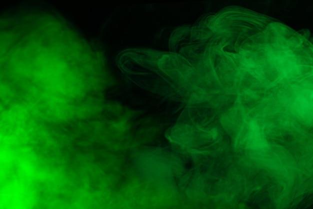 Grüner dampf auf schwarzem hintergrund. platz kopieren.