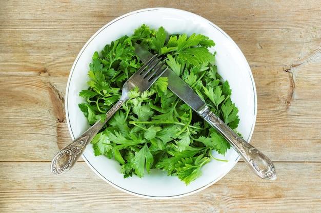 Grüner detox-salat aus petersilie-koriander-kräutern auf tellergabelmesser auf altem holztisch