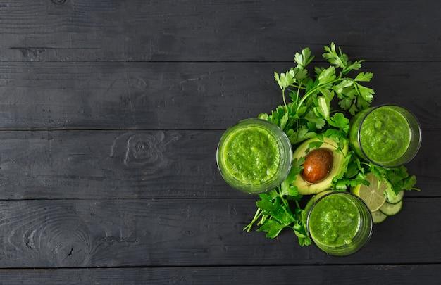 Grüner detox smoothie auf einer draufsicht des dunklen hölzernen hintergrundes