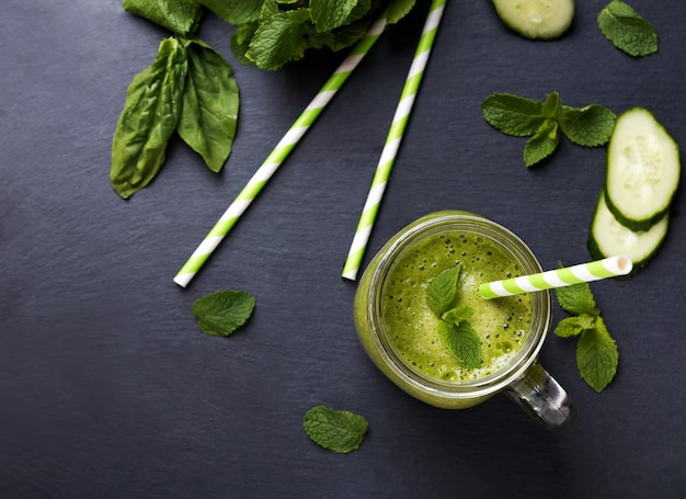Grüner detox-smoothie in einem glas auf schwarzem hintergrund, ansicht von oben