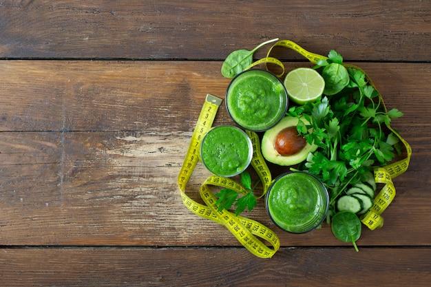 Grüner detox smoothie mit messendem band auf hölzernem hintergrund detox-saftkonzept