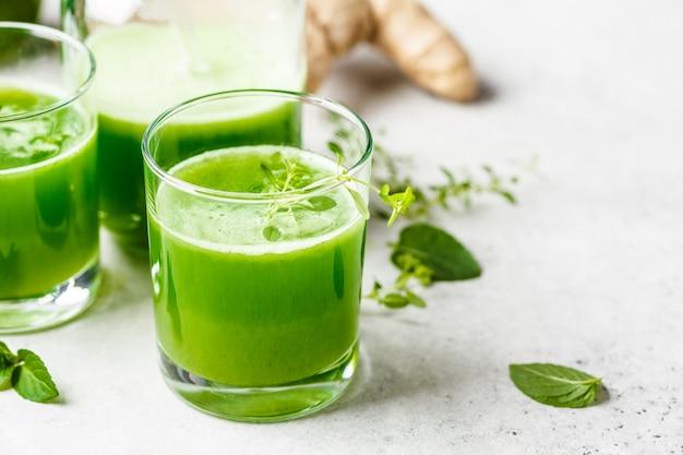 Grüner detoxsaft mit ingwer und minze in gläsern und gläsern