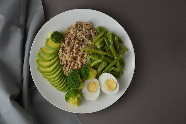 Grüner detoxsalat, quinoa und grünes gemüse - erbsen, avocado, brokkoli und eier.