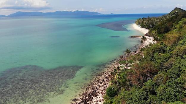 Grüner dschungel und felsiger strand am meer oder am meer. tropischer regenwald, sandiges ufer der paradiesinsel.