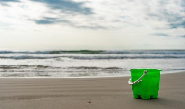 Grüner eimer auf dem strandsand, der das meer gegenüberstellt