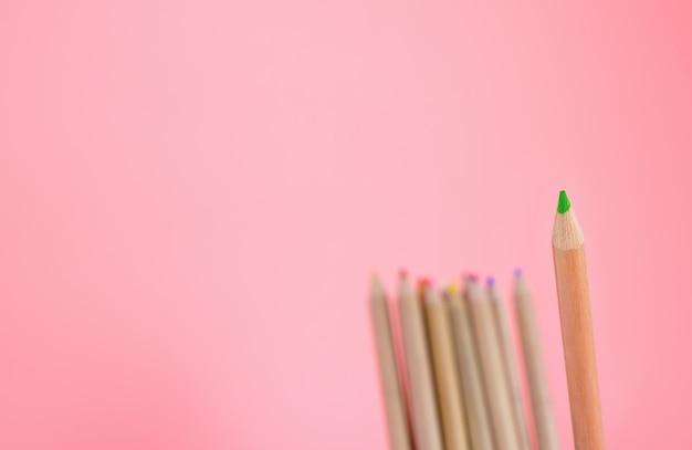Grüner farbbleistift haften heraus auf rosa kopienraum