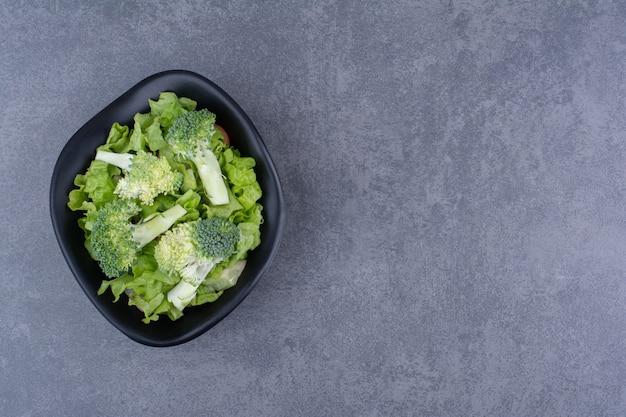 Grüner frischer brokkoli isoliert auf blauer oberfläche