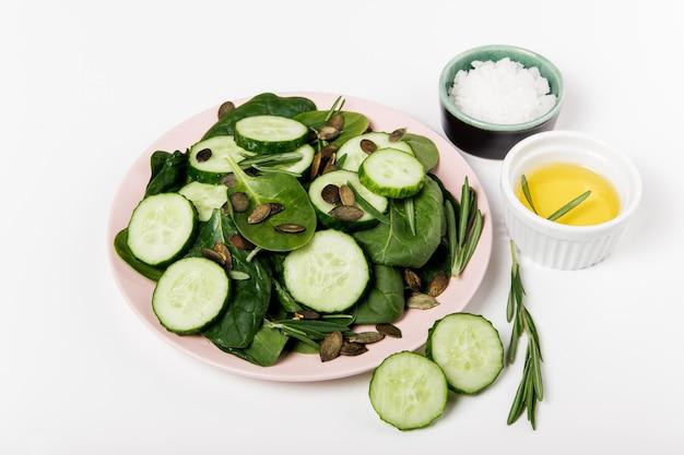 Grüner frischer salat aus spinat, gurke und kürbiskernen.