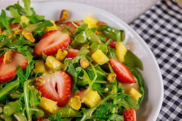 Grüner frischer salat mit rucola, erdbeeren, mango und pistazien