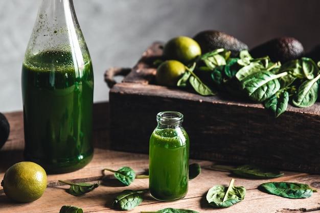 Grüner frischer smoothie im glas mit obst, gemüse und gemüse in alter holzkiste