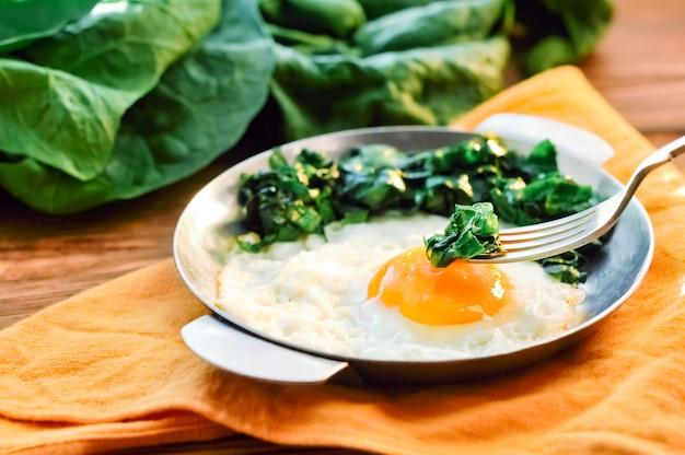 Grüner gekochter spinat mit spiegelei auf eisenpfannenplatte. gesundes frühstück mit spiegeleiern auf holztisch serviert mit orangefarbener serviette, gabel und spinatblättern, zutaten. nahansicht.