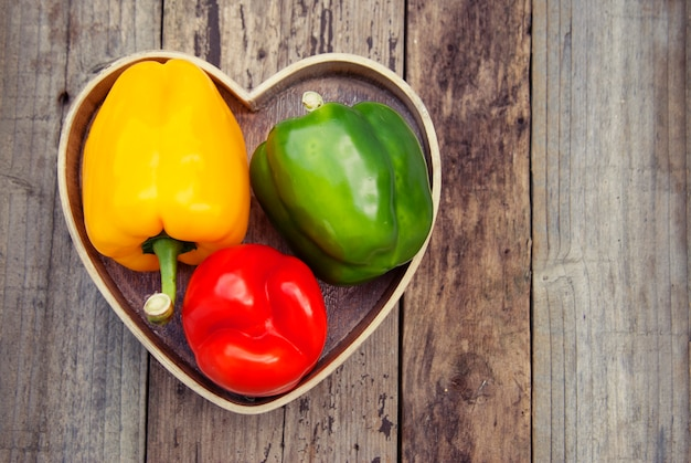 Grüner, gelber und roter grüner pfeffer über rustikalem strukturiertem hölzernem. gesundes gemüse, essen.