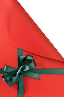 Grüner geschenkbandbogen auf einfachem rotem hintergrundpapier