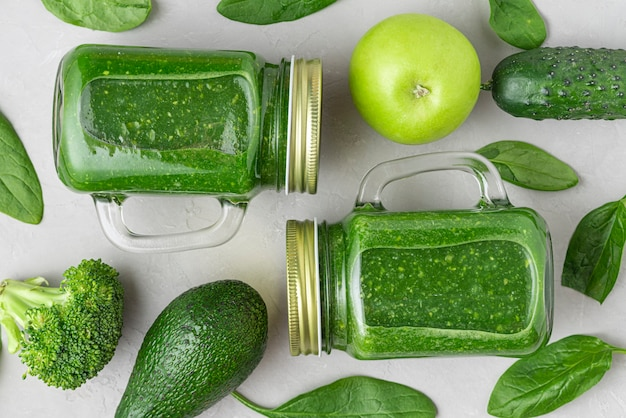 Grüner gesunder entgiftungs-smoothie mit frischem gemüse und früchten in den gläsern auf konkretem hintergrund. flach liegen. draufsicht. gesundes entgiftungsfrühstückskonzept