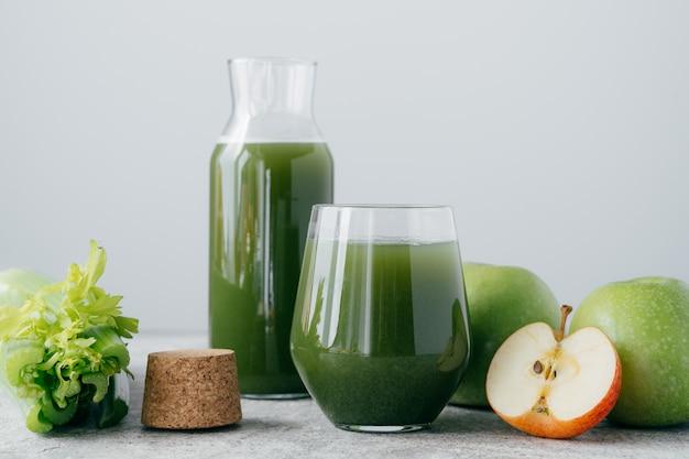 Grüner gesunder sellerie und apfelsaft in den glaswaren.