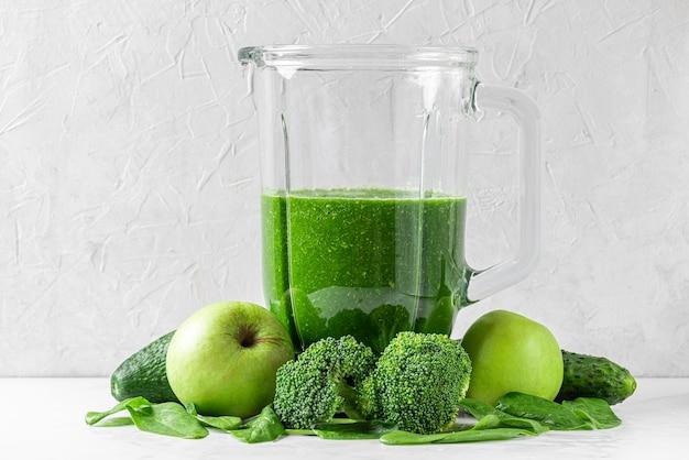 Grüner gesunder smoothie im mixer aus brokkoli, spinat, apfel und gurke. gesundes entgiftungsfrühstück. nahansicht