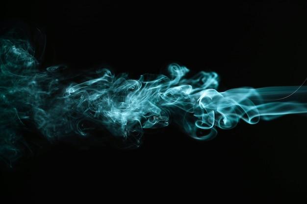 Grüner gewellter rauch auf schwarzem hintergrund