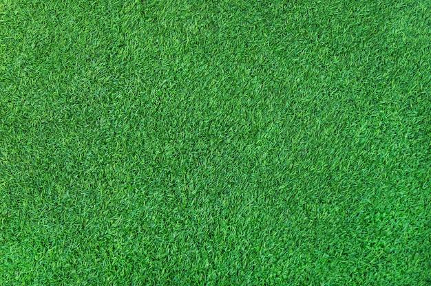Grüner grashintergrund des künstlichen grünen rasengrases auf dem boden