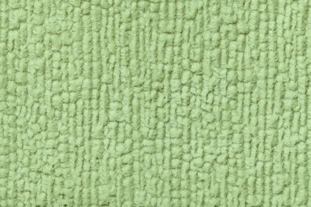 Grüner hintergrund des weichen, flaumigen stoffes. beschaffenheit der textilnahaufnahme