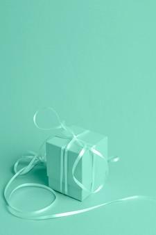 Grüner hintergrund mit isometrischem geschenk