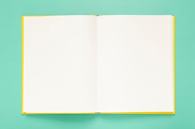 Grüner hintergrund mit leerem notizbuch