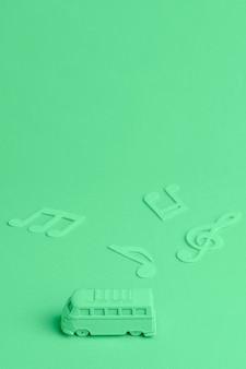 Grüner hintergrund mit spielzeugbus und musikanmerkungen