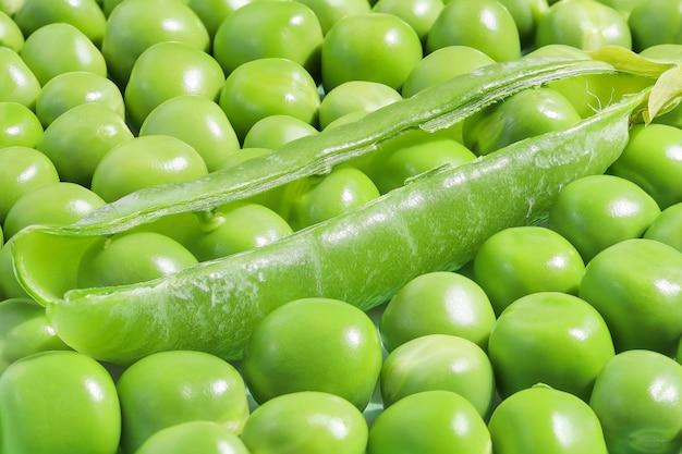 Grüner hintergrund, vollständig gefüllt mit frischen erbsen und einer schote in der mitte der oberfläche