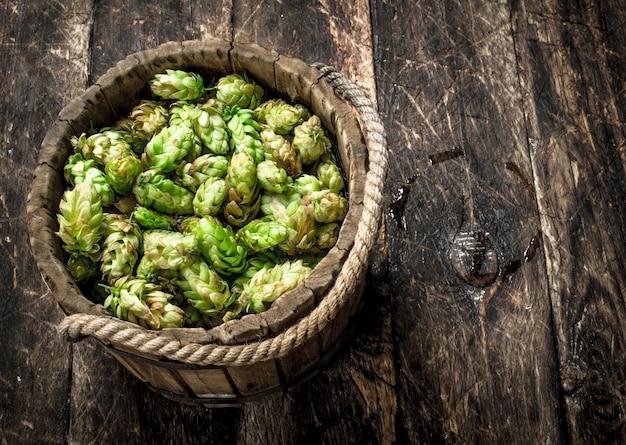 Grüner hopfen für bier in einem hölzernen eimer. auf einem hölzernen hintergrund.