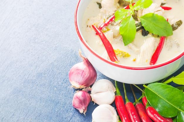 Grüner hühnercurry mit thailändischem traditionellem lebensmittel des rohen würzigen bestandteils auf hellblauem hintergrund