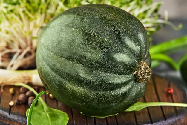 Grüner kabocha-kürbis mit zwiebeln und knoblauch auf einem hölzernen träger. gesundes essen