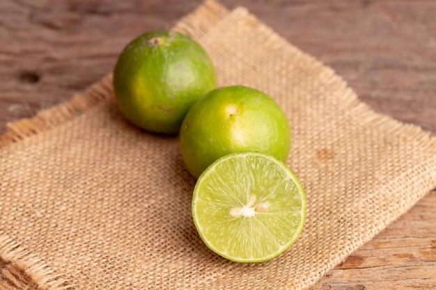Grüner kalk- und samenplatz auf gesponnenem sack auf dem holztisch in einer küche