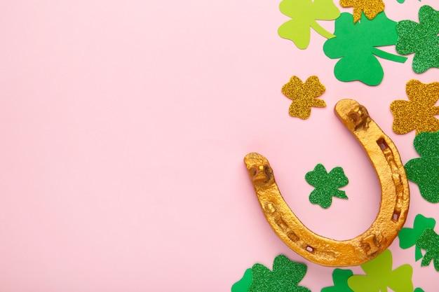 Grüner klee und goldenes hufeisen auf rosa hintergrund für st. patrick's day holiday. draufsicht.