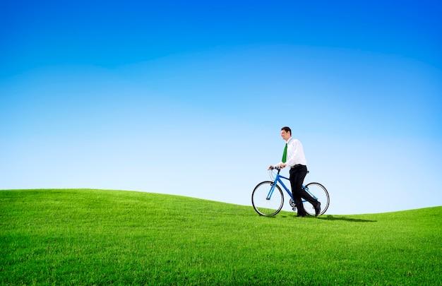 Grüner konzept-geschäftsmann, der draußen fahrrad fährt
