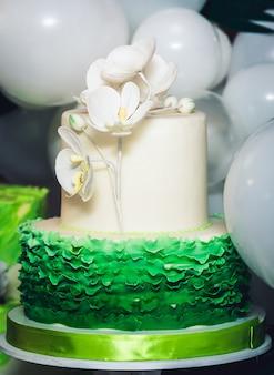 Grüner kuchen verziert mit phalaenopsis-blumen