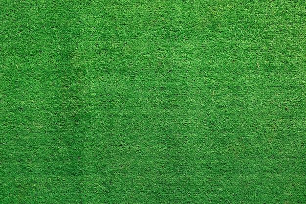 Grüner kunstrasen. hintergrund des frischen grünen grases.
