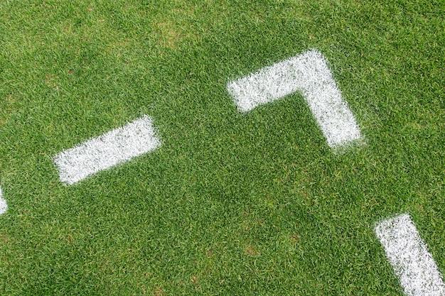 Grüner kunstrasenrasenfußballfußballhintergrund mit weißer liniengrenze. draufsicht