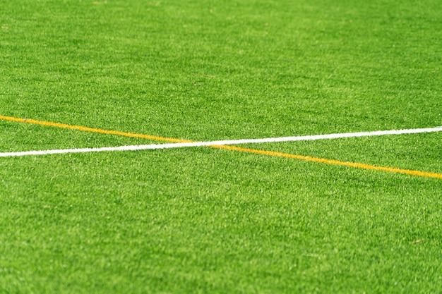 Grüner kunstrasenrasenfußballfußballhintergrund mit weißer und gelber liniengrenze. draufsicht
