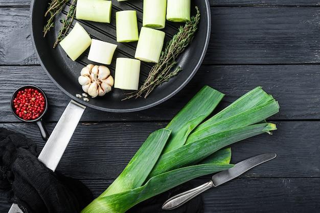 Grüner lauch sultan gehackt oninon auf grillpfanne ungekocht mit kräuterzutaten, auf schwarzer hölzerner tischoberansicht.
