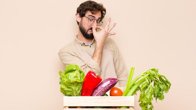 Grüner lebensmittelhändler, der sich angewidert fühlt und die nase hält, um einen üblen und unangenehmen gestank zu vermeiden