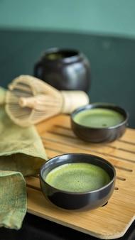 Grüner matcha-tee in traditioneller tasse auf bambustablette und grüner serviette
