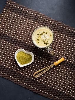 Grüner matcha tee lattebecher auf dunkelheit