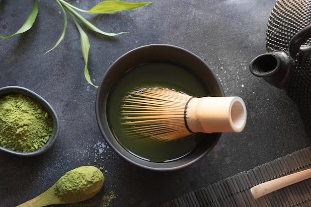 Grüner matcha tee und bambus der zeremonie wischen auf schwarzer tabelle. ansicht von oben. platz für text.