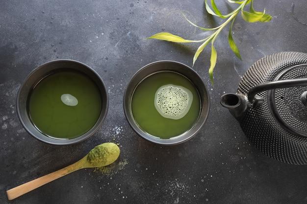 Grüner matcha tee und bambus der zeremonie wischen auf schwarzer tabelle. ansicht von oben.