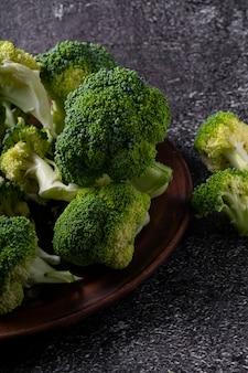 Grüner mini-brokkoli auf braunem teller