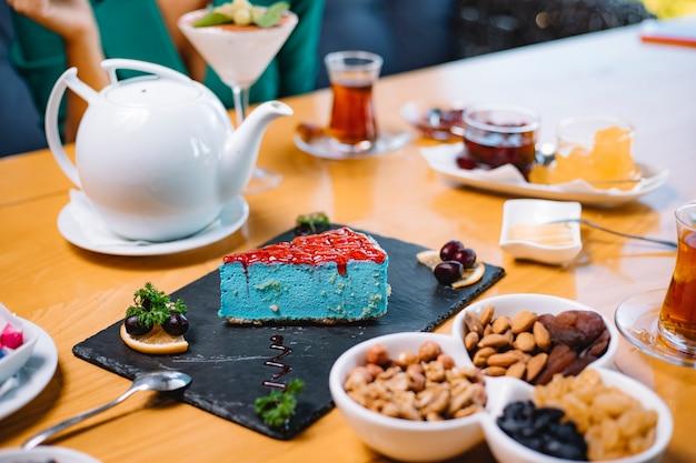 Grüner minzkäsekuchen der seitenansicht auf einer schwarzen bordüre, die mit tee auf dem tisch serviert wird