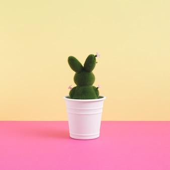 Grüner osterhase dekoriert mit blumen im blumentopf auf leuchtend gelbem und rosa hintergrund. minimalistisches konzept. quadrat mit kopienraum.
