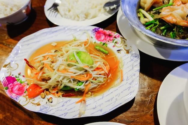 Grüner papaya-salat (som tum thailändisch) auf dem tisch