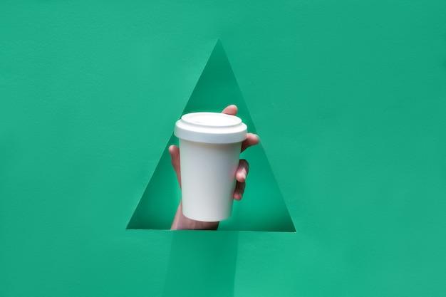 Grüner papiertisch, tasse aufbewahren. wiederverwendbarer öko-kaffee-reisebecher, bambusbecher mit deckel in der hand durch dreieckiges papierloch