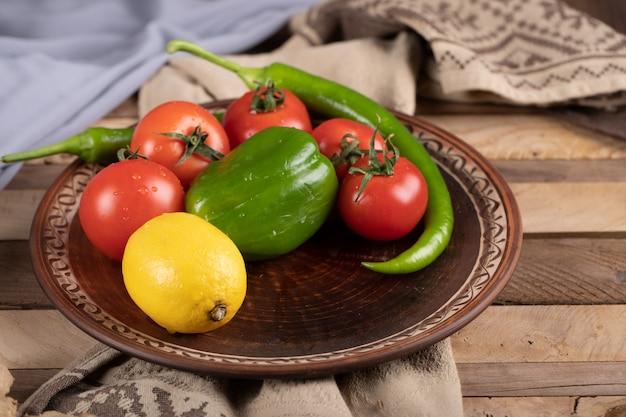 Grüner pfeffer mit tomaten und einer zitrone in einer braunen platte