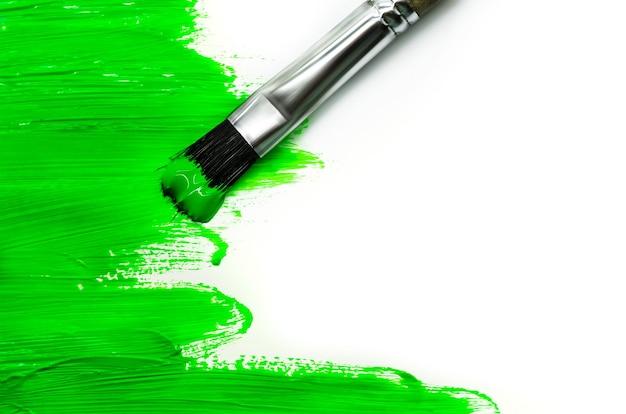 Grüner pinsel an einer weißen wand